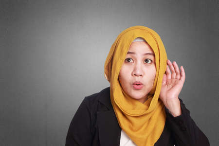 Portrait of young muslim businesswoman hearing gesture, put hand on ear, listening carefully Stock Photo