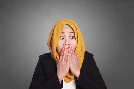 Young attractive muslim businesswoman wearing hijab covering her mouth with hands, shocked surprised expression