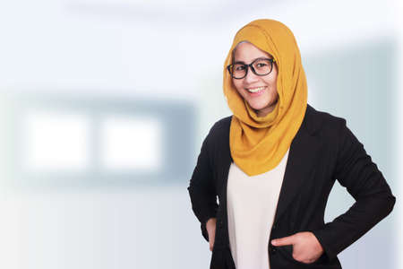 Portrait of muslim businesswoman wearing hijab standing and smiling, hands on hips, blurred defocus background