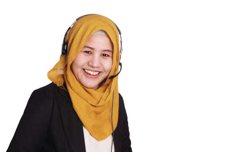 Portrait of beautiful young muslim lady wearing hijab, call center operator consultant smiling with headphones isolated on white Standard-Bild