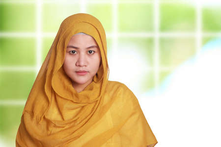 Portrait of beautiful muslim woman wearing hijab smiling over blurred background  Stock Photo