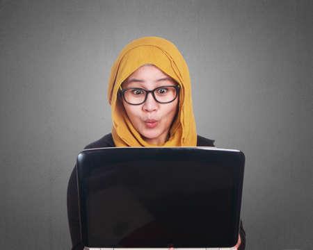 Porträt der muslimischen Geschäftsfrau Hijab unter Verwendung des Laptops mit entsetztem überraschten aufgeregten Gesichtsausdruck Geste