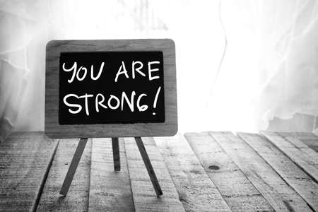 You are strong. Motivational inspirational quotes words. Wooden background