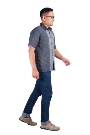 Full body portrait of young Asian man wearing batik shirt and glasses walking side view and smiling, isolated on white