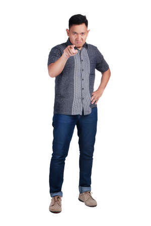 Young Asian man wearing blue jeans and batik shirt, angry man pointing gesture. Isolated on white. Full body portrait Stok Fotoğraf