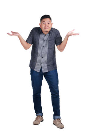 I don't know. Young Asian man wearing batik isolated on white background being at a loss, showing helpless gesture with arm and hands, mouth curved as if he does not know what to do Foto de archivo
