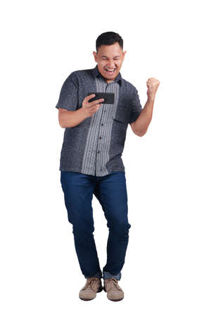 Young Asian man wearing blue jeans and batik shirt playing his phone with a happy expression. Isolated on white. Full body portrait Stock Photo