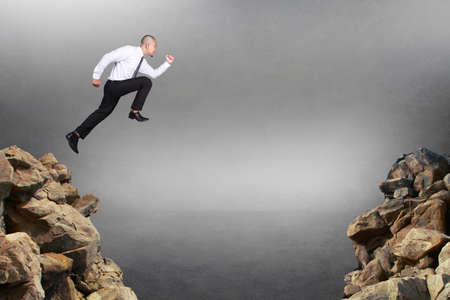 Composite image. Businessman running jumping trough obstacle gap, business risk concept