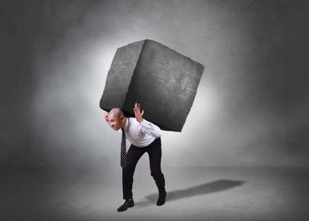 Composite image. Stress overwork and pressure in business concept. Businessman walking and carrying heavy stone on his back. Grunge background