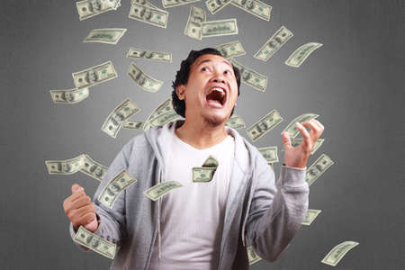 Successful young Asian man wearing jacket, Smiling and laughing celebrating victory, Under money rain