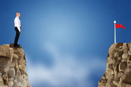 Businessman standing on the edge of a cliff looking to his business goal target over gap distance Banque d'images