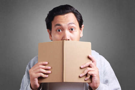 Young Asian man wearing white shirt and gray jacket covering his mouth with a book, surprised expression. Background on gray. Close up head and shoulders