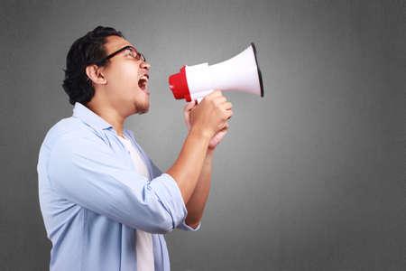 Joven asiático con camisa blanca y azul gritando con megáfono, expresión enojada. Cerrar el retrato del cuerpo