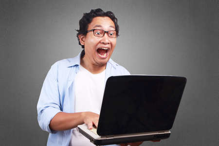 Young Asian man wearing white and blue shirt screaming, funny expression looking at a laptop. Close up body portrait Archivio Fotografico