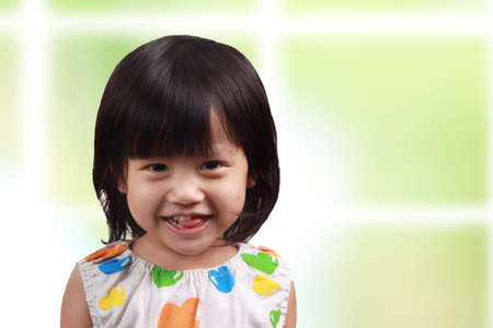Young asian cute little girl smiling cheerfully Фото со стока