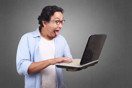 Young Asian man wearing white and blue shirt take out his tounge, funny expression looking at laptop. Archivio Fotografico