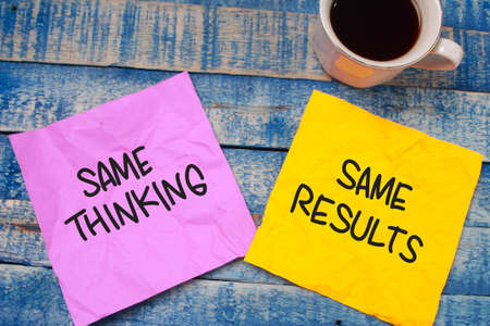 Same thinking same results words letter, written on piece of memo paper, work desk top view. Motivational self development business typography quotes concept