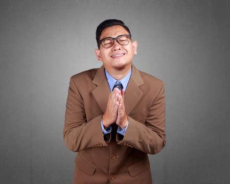 Young Asian businessman wearing suit regret, apologize gesture. Close up body portrait