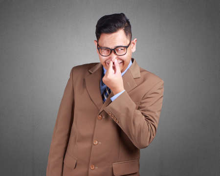 Young Asian businessman wearing suit smell something bad, disgusted expression. Close up body portrait Stock Photo
