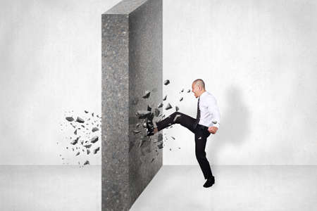 Businessman breaking wall of obstacle by kick. Business challenge conquering adversity concept