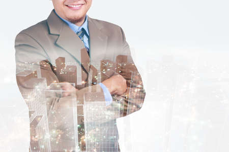 Double exposure image of businessman standing with crossed arms overlay with cityscape image. The concept of modern life, business, city life and internet of things Standard-Bild