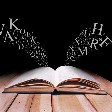 Educational concept. Opened book on wooden table with alphabet letters flying over against black dark background Stock Photo