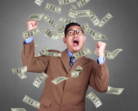 Joven empresario asiático vistiendo traje gesto ganador. Retrato de cuerpo de cerca. Signo de caída de dinero