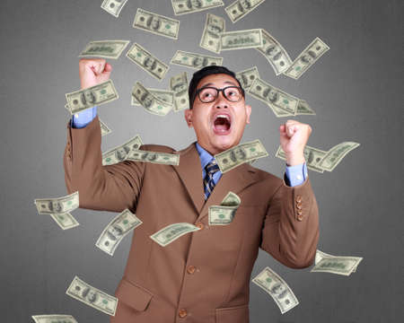 Young Asian businessman wearing suit winning gesture. Close up body portrait. Money falling sign