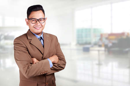 Young Asian businessman wearing suit and glasses smiling looking at a camera, crossed arm Banque d'images
