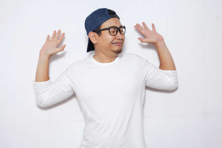 Photo image of young funny Asian man afraid expression with hands raised up, surrender, while standing over white background