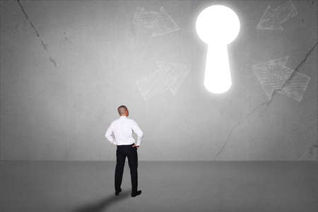 Rear view of businessman facing light keyhole on the wall. Concept of business challenge. Success future hope conquering adversity