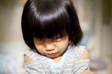 Imagen de retrato de la pequeña niña asiática se enoja mucho, mirando a la cámara Foto de archivo