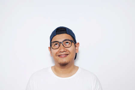 Photo image of young Asian man looked happy, thinking and looking up, having good idea. Half body portrait against white wall with copy space Reklamní fotografie