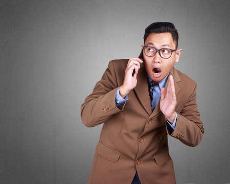 Retrato de atractivo joven empresario asiático hablando por su teléfono, recibiendo malas noticias, expresión de asombro, sobre fondo grunge