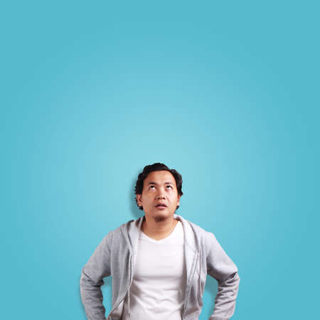 Young Asian man thinking expression, eyes glance to the top, over blue background with copy space Stock Photo