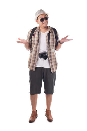 Traveling people concept. Portrait of Asian male backpacker tourist wearing hat, black sunglasses, camera and backpack isolated on white. Full body portrait. Confuse gesture shrug shoulder
