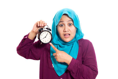 Young Asian businesswoman wearing suit and hijab worried by time when looking at a clock. Isolated on white. Close up body portrait Imagens