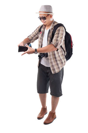 Traveling people concept. Portrait of Asian male backpacker tourist wearing hat, black sunglasses, camera and backpack isolated on white. Full body portrait. Broke empty wallet