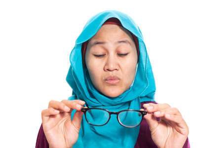 Portrait of muslim businesswoman wearing hijab adjusting her eyeglasses trying to see focus, eye sight trouble, blur vision, isolated on white