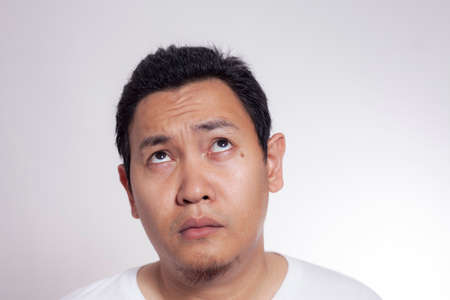 Photo image of funny Asian man thinking and looking up, close up headshot portrait over white background