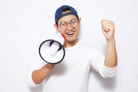 Young Asian man wearing casual white shirt using megaphone, shouting and smiling. Close up body portrait. Marketing promotion concept