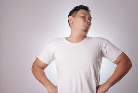 Portrait of funny young Asian man shows his over confidence, hands on hips with arrogant gesture