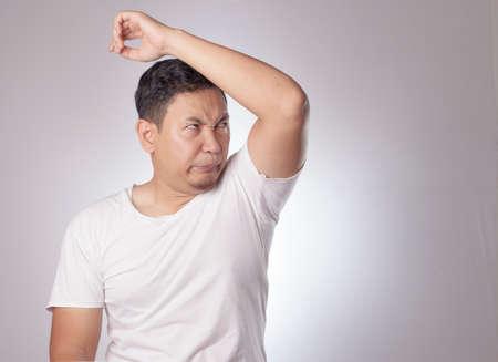 Porträt eines lustigen jungen asiatischen Mannes, der seinen eigenen Achselgeruch überprüft, schlechtes Körpergeruchsproblem