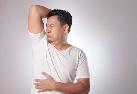 Portrait of funny young Asian man checking his own armpit smell, bad body odor problem