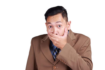 Close up portrait of attractive Asian businessman closing his mouth with fingers. Worried gesture, cant say anything. Shocked surprised to hear bad news or gossip