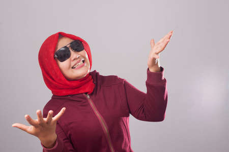 Portrait of Asian muslim lady wearing black sunglasses in red suit and hijab shows refusal or denial gesture, shoulder shrug, I don't know expression Foto de archivo