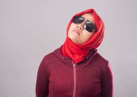 Portrait of tough arrogant Asian muslim lady wearing black sunglasses in red suit and hijab Stock Photo