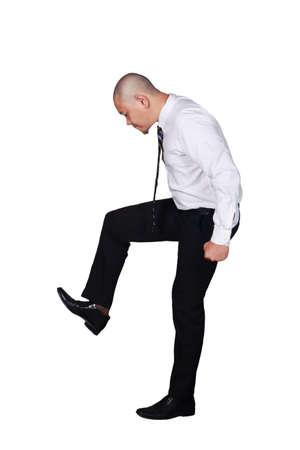 Joven empresario vistiendo traje blanco y pantalón negro pisando fuerte gesto. Aislado en blanco. Retrato de cuerpo entero