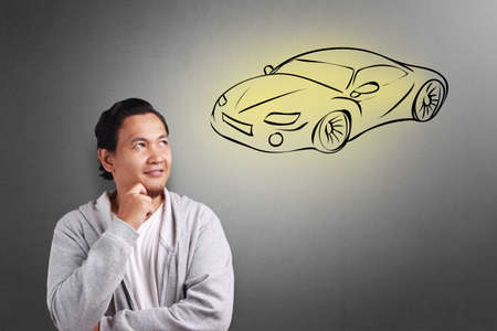 Portrait of young Asian man smiling thinking and dreaming of having a sports car