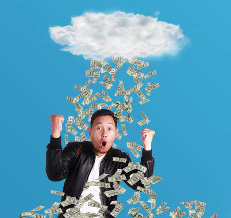 Portrait of happy successful young Asian billionaire man smiling happily under rain of money. Wealth investment economic concept